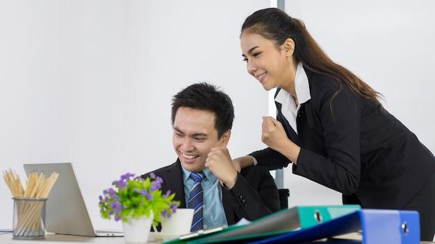 Konzeptglückwunsch mit erfolgreichem job. asiatische büroangestellte sehen glücklich und glücklich mit der arbeit aus. asiatische frau und mann mitarbeiter paar teamkollegen lächelnd und laptop betrachten fühlen sich im büro sehr glücklich.