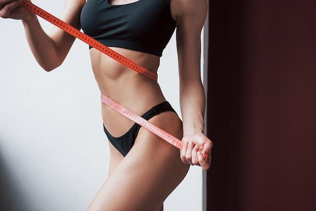 Konzeption der gesundheitsfürsorge. nahaufnahme des schlanken körpers der fitness des jungen mädchens, der durch das band misst