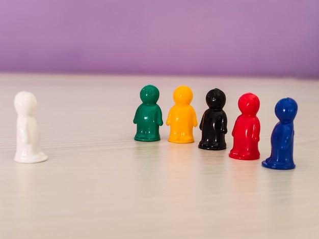 Konzeption - lidership, leader in einem team, diversity, spielfiguren oder spielfiguren in einer geschäftssituation. farbige chips von tabletop-spiel in der form der kleinen männer