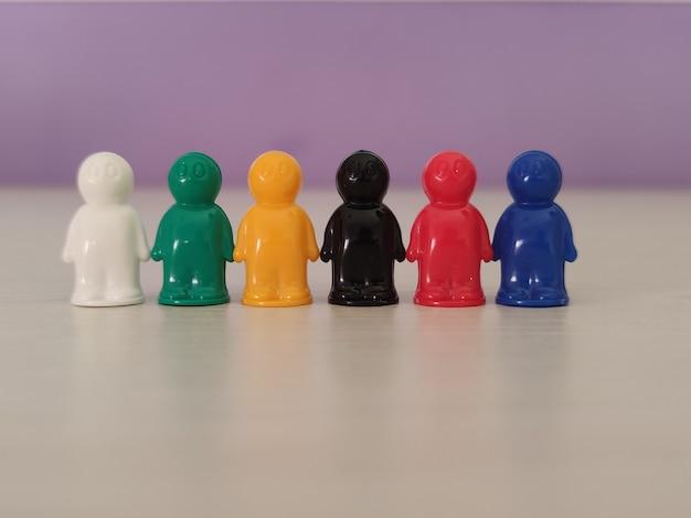 Konzeption - partnerschaft, kooperation, spielfiguren oder spielfiguren in einer geschäftssituation. farbige chips von tabletop-spiel in der form der kleinen männer