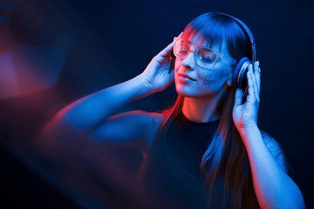Konzeption von cyberpank und futurismus. studioaufnahme im dunklen studio mit neonlicht. porträt des jungen mädchens