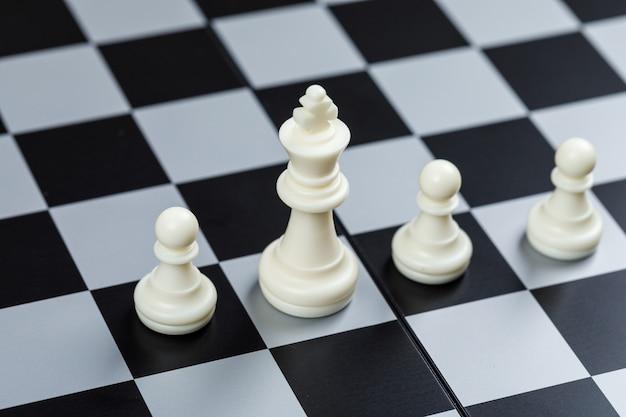 Konzeption von strategie und schach. auf schachbrettoberfläche hochwinkelansicht. horizontales bild