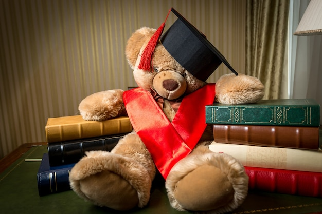Konzeptionelle aufnahme der kindererziehung. brauner teddybär in abschlusskappe, der sich auf bücher stützt