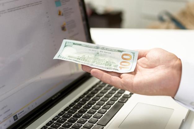 Konzeptionelle aufnahme der zahlung im internet. mann hält banknote in der hand vor pc-bildschirm