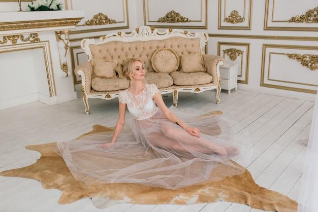 Konzeptionelle hochzeit, der morgen der braut im europäischen stil. boudoir kleid, gebühren im innenraum. weißer minimalismus für die braut