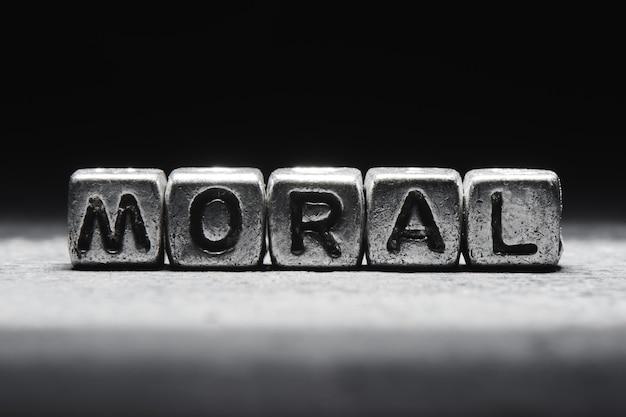 Konzeptionelle inschriftenmoral auf metallwürfeln auf einer schwarzen grauen hintergrundnahaufnahme lokalisiert