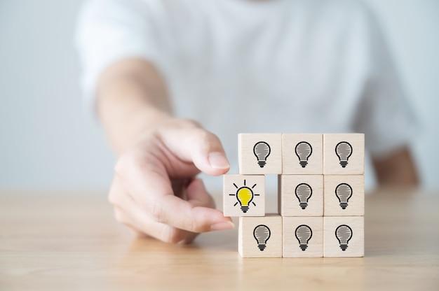 Konzeptionelle kreative idee und innovation. handverlesener holzwürfelblock mit glühbirnensymbol