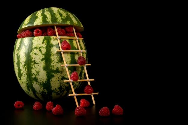 Konzeptionelle wassermelone gefüllt mit himbeeren, die die treppe auf einem schwarzen hintergrund klettern