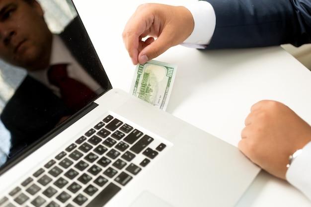 Konzeptioneller geschäftsmann, der digitale geldüberweisung empfängt. mann zieht dollarschein aus laptop
