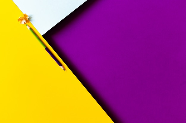 Konzeptioneller minimalistischer papierhintergrund mit zweifarbigem bleistift und schnitzeln vom schärfen. zurück zu schule und bildungskonzept.