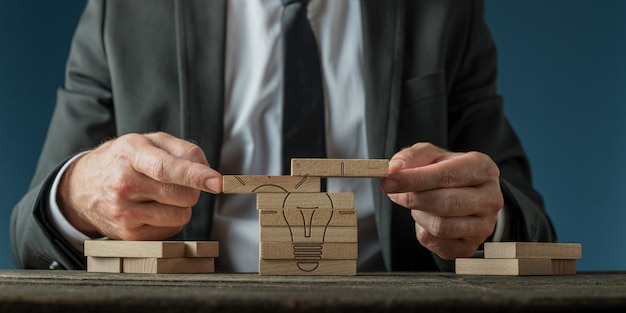Konzeptionelles bild der geschäftsvision und -strategie - geschäftsmann, der eine glühbirne zusammenbaut, die auf holzstiften gezeichnet wird.