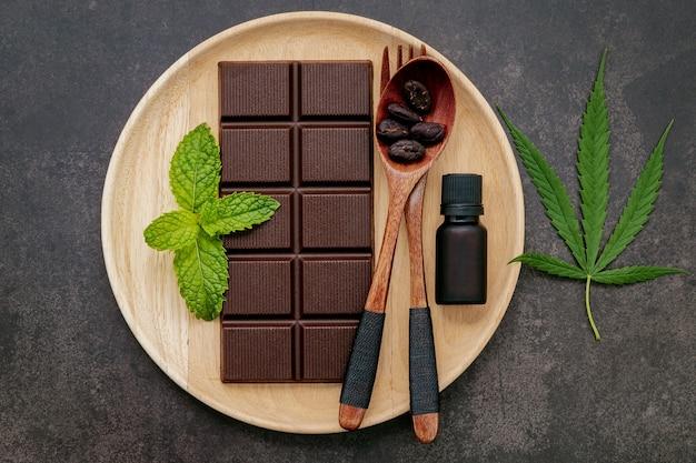 Konzeptionelles bild des essens von cannabisblatt mit dunkler schokolade und gabel auf dunklem beton.