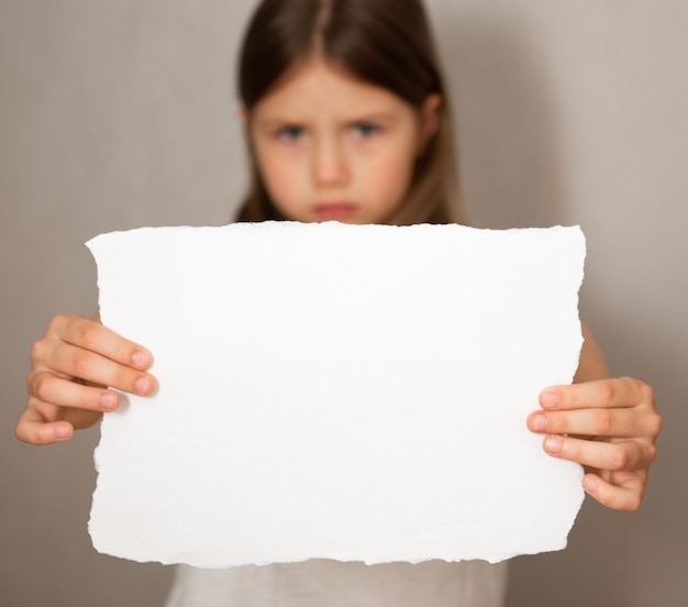 Konzeptionelles bild eines traurigen niedergeschlagenen kleinen mädchens, hält ein leeres blatt papier auf grauem hintergrund