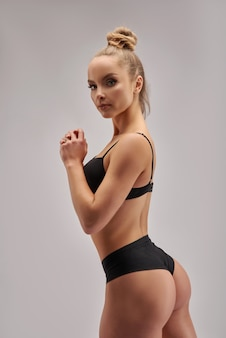 Konzeptionelles nahaufnahmeporträt der sportlichen jungen frau der fitness in der schwarzen sportbekleidungskleidung, die ihren gut ausgebildeten körper zeigt selbstbewusster weiblicher fit-bodybuilder isoliert auf weißer kopie