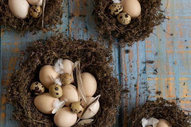 Konzeptionelles stillleben mit wachteleiern und hühnereiern im nest auf dunklem hintergrund