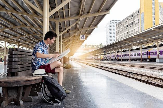 Konzeptlebensstilreisen oder -reise: junge asiatische mann-reisender blick auf die karte während des wartens auf den zug kommt am bahnhof an.