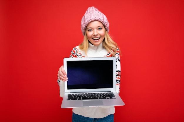 Konzeptporträtaufnahme der schönen lächelnden blonden jungen frau, die computer-laptop mit leer hält