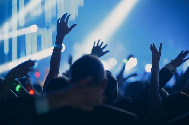 Konzert-, event- oder partykonzept. menschen mit den händen vor ort, scheinwerfer, farbiges licht.