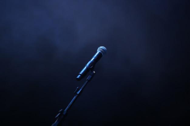 Konzertmikrofon auf dunkelblauem rauchhintergrund.