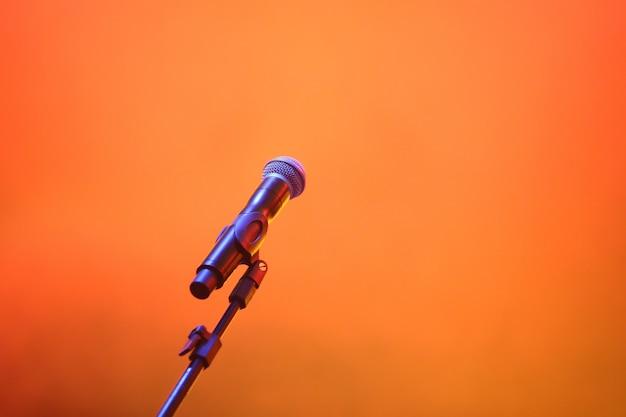 Konzertmikrofon auf orangefarbenem rauchhintergrund.