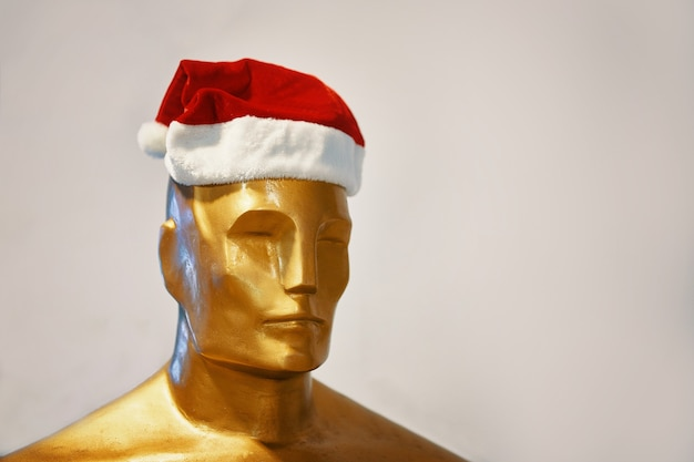 Kopf der goldenen figur des mannes im weihnachtsmann-hut-akademiepreis in der weihnachtsdekoration lustiger oscar