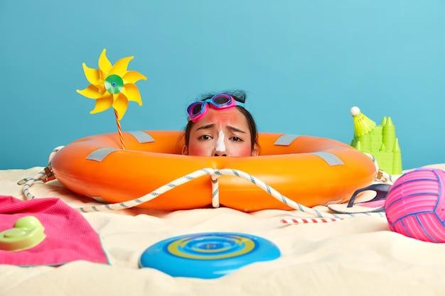 Kopf der jungen frau mit sonnenschutzcreme auf gesicht umgeben von strandaccessoires