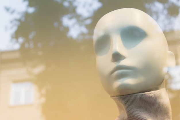 Kopf der weiblichen schaufensterfigur aus dem schaufenster mit verschwommenen reflexionen