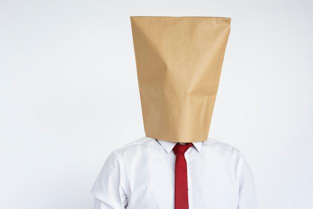 Kopf des anonymen mannes bedeckt mit papiertüte