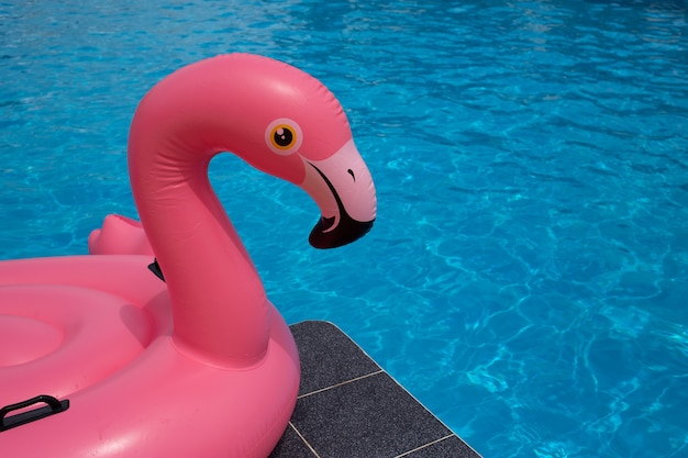 Kopf des flamingopools schwimmt im blauen wasserhintergrund des swimmingpools