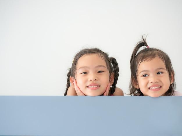 Kopf des glücklichen asiatischen netten mädchens zwei, das über dem brett lächelt