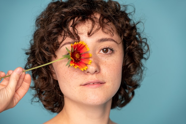 Kopf einer schönen jungen sommersprossigen brünetten frau, die ein wunderschönes gänseblümchen mit dem rechten auge hält, während sie dich auf blau ansieht