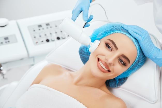 Kopf und schultern der frau, die auf couch in der blauen kappe in der kosmetischen klinik liegt, beiseite schaut und lächelt. doktor hält instrument zum bürsten nahe ihrem gesicht