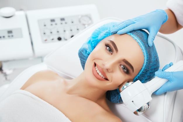 Kopf und schultern der frau, die auf couch in der blauen kappe in der kosmetischen klinik liegt, kamera betrachtet und lächelt. doktor hält spa heißen / kalten hammer nahe ihrem gesicht