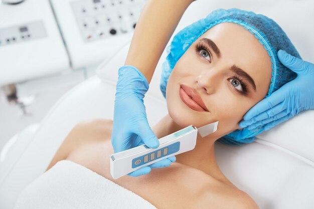 Kopf und schultern der frau, die auf couch in der blauen kappe in der kosmetischen klinik liegt und beiseite schaut, nahaufnahme. die hände des doktors in blauen handschuhen halten ultraschall-scraber in der nähe ihres gesichts