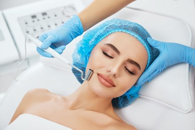 Kopf und schultern der frau, die auf couch in der blauen kappe in der kosmetischen klinik mit geschlossenen augen liegt. die hände des doktors in blauen handschuhen halten die elektrode zur galvanisierung in der nähe ihres gesichts