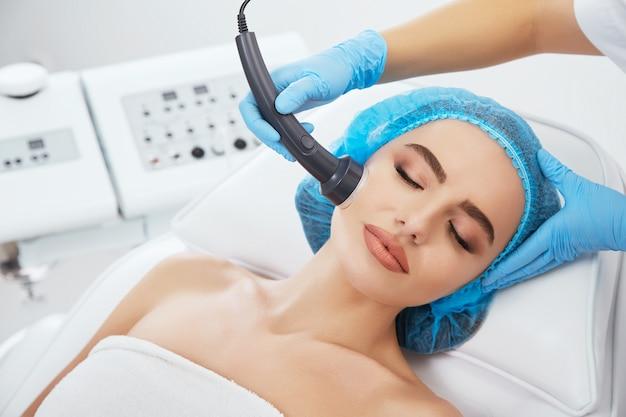 Kopf und schultern der frau, die auf couch in der blauen kappe in der kosmetischen klinik mit geschlossenen augen liegt. die hände des doktors in blauen handschuhen halten die ultraschall-phonophorese in der nähe ihres gesichts