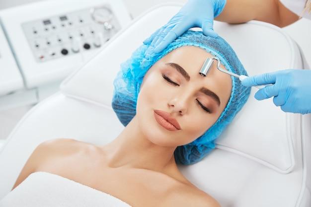 Kopf und schultern der frau, die auf couch in der blauen kappe in der kosmetischen klinik mit geschlossenen augen und lächelnd liegt. die hände des doktors in blauen handschuhen halten die elektrode zur galvanisierung in der nähe ihres gesichts