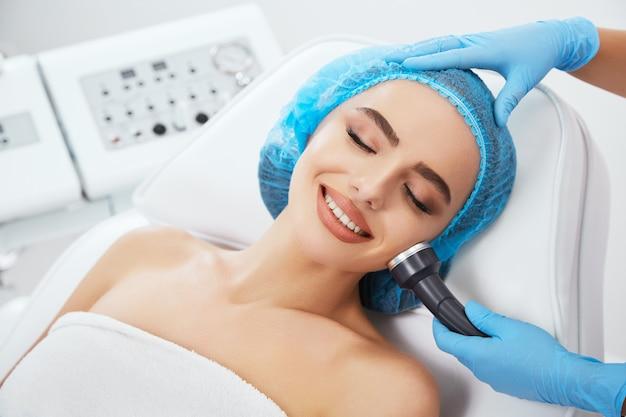 Kopf und schultern der frau, die auf couch in der blauen kappe in der kosmetischen klinik mit geschlossenen augen und lächelnd liegt. die hände des doktors in blauen handschuhen halten die ultraschall-phonophorese in der nähe ihres gesichts