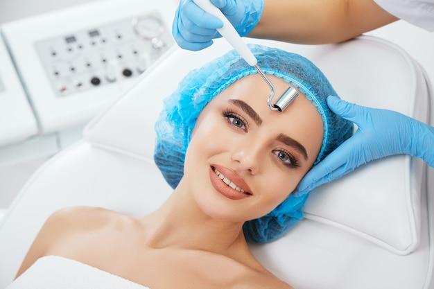 Kopf und schultern der frau, die auf der couch in der blauen kappe in der kosmetischen klinik und lächelnd liegt. die hände des doktors in blauen handschuhen halten die elektrode zur galvanisierung in der nähe ihres gesichts