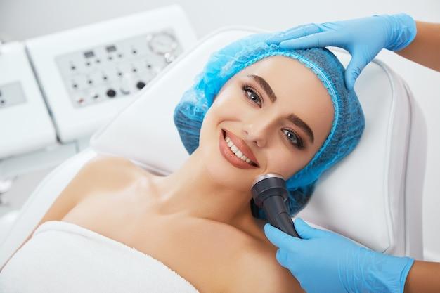 Kopf und schultern der frau, die auf der couch in der blauen kappe in der kosmetischen klinik und lächelnd liegt. die hände des doktors in blauen handschuhen halten die ultraschall-phonophorese in der nähe ihres gesichts