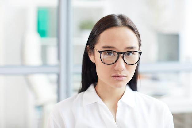 Kopf und schultern porträt der jungen asiatischen geschäftsfrau, die brille trägt, während im modernen weißen büro aufwirft