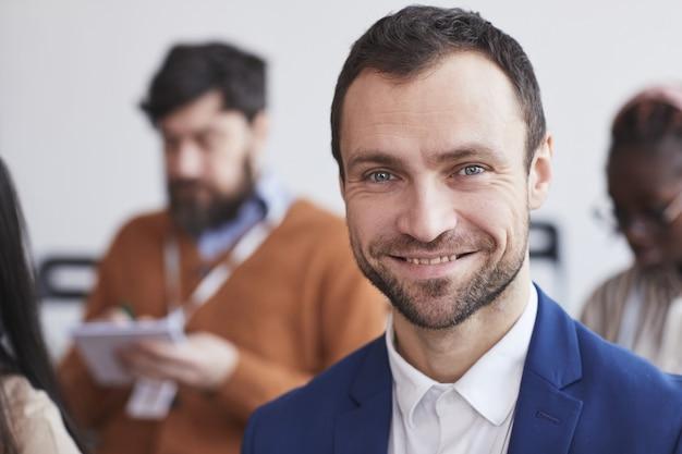 Kopf- und schulterporträt eines lächelnden geschäftsmannes, der die kamera mit dem publikum auf der geschäftskonferenz im hintergrund betrachtet, kopienraum