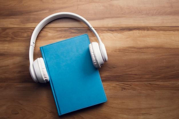 Kopfhörer auf buch auf holztisch