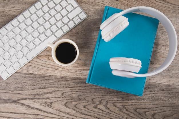 Kopfhörer auf buch mit tastatur und kaffee auf tisch