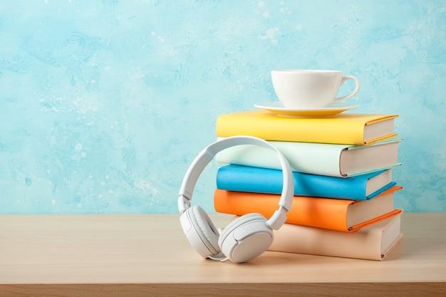 Kopfhörer, bücherstapel und tasse auf einem tisch