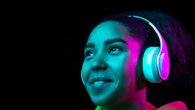 Kopfhörer. das porträt der afroamerikanerfrau lokalisiert auf dunklem studiohintergrund im mehrfarbigen neonlicht. schönes weibliches modell. konzept der menschlichen emotionen, gesichtsausdruck, verkauf, werbung, mode.