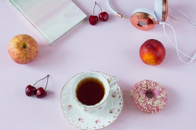 Kopfhörer, ein notizbuch, kirschen, äpfel, pfirsiche, eine tasse tee, ein donut