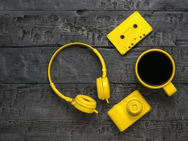 Kopfhörer, kaffee, eine kamera und eine kassette auf einem holztisch. kreatives frühstück.