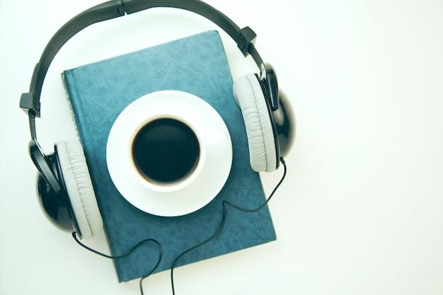 Kopfhörer, kaffee und buch auf weißem tisch