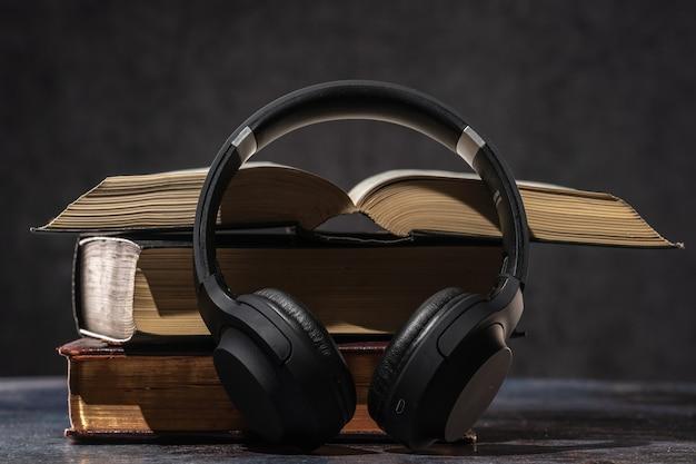Kopfhörer liegen neben alten büchern. hörbuch-konzept.